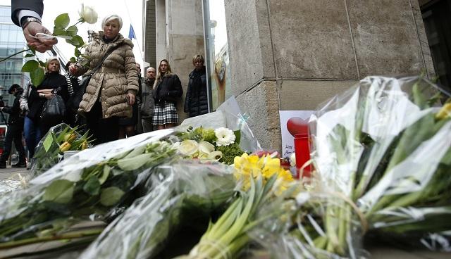 Muž kladie bielu ružu na pamiatku obetí teroristických útokov pred vchodom stanice metra Maelbeek v Bruseli 24. marca 2016