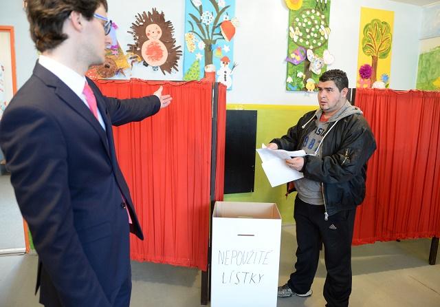Na snímke vpravo volič s nepoužžitými hlasovacími lístkami vo volebnej miestnosti vo voľbách do Národnej rady SR na koššickom rómskom sídlisku Luník IX v Koššiciach v sobotu 5. marca 2016