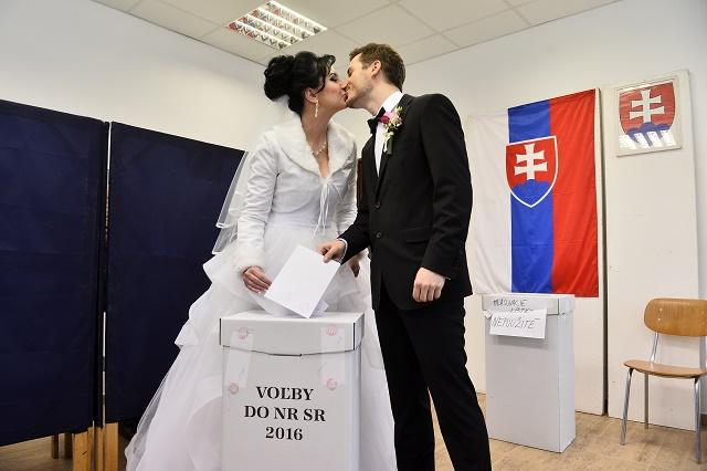 ŽŽeních Ondrej ŠŠulc (vpravo) a nevesta Petra Schönová sa bozkávajú pri vhadzovaní obálok s hlasovacími lístkami do volebnej schránky vo voľbách do Národnej rady SR vo volebnej miestnosti v Dubnici nad Váhom 5. marca 2016