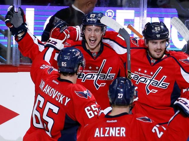 Hráč Washingtonu Capitals Jay Beagle (83) oslavuje so spoluhráčmi Andre Burakovským (65), Karlom Alznerom (27) a Marcusom Johanssonom (90) gól do bránky Philadelphie Flyers v úvodnom zápase 1. kola play off hokejovej zámorskej NHL