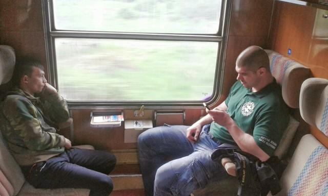 Člen bezpečnostnej hliadky z ĽSNS (vpravo) a oproti nemu sediaci Róm v kupé kontrolovaného vlaku