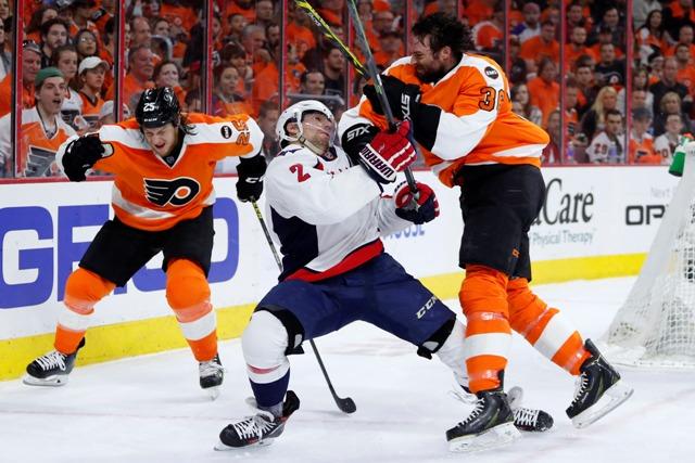 Hráč Flyers Colin McDonald (vpravo) v kolízii s hráčom Capitals Mattom Niskanenom (v strede) vo štvrtom zápase štvrťfinále Východnej konferencie hokejovej NHL Washington Capitals - Philadelphia Flyers
