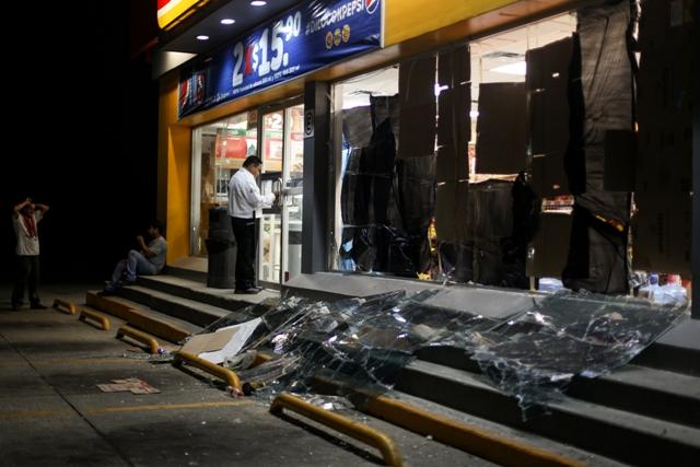 Na snímke ochrankár stráži obchod, ktorý bol poškodený výbuchom v petrochemickom podniku mexickej štátnej ropnej spoločnosti Pemex v mexickom Coatzacoalcose