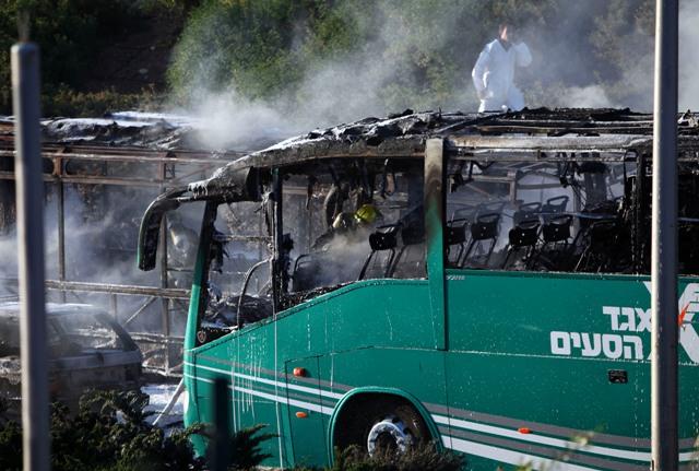 Izraelský hasič zasahuje pri zhorenom autobuse v Jeruzaleme 18. apríla 2016