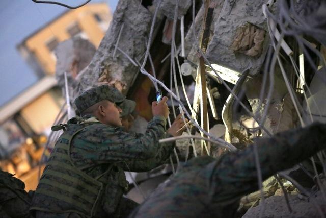Vojak si svieti mobilom počas pátrania po preživších v troskách zrútenej budovy po silnom zemetrasení s magnitúdou 7,8 na ulici v Portovieju