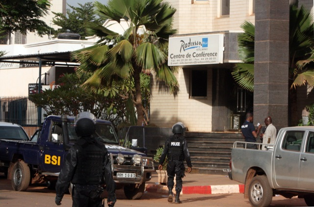Malijskí policajti kráčajú pred jedným z vchodov do hotela Radisson Blu v malijskom meste Bamako 20. novembra 2015 po útoku ozbrojencov