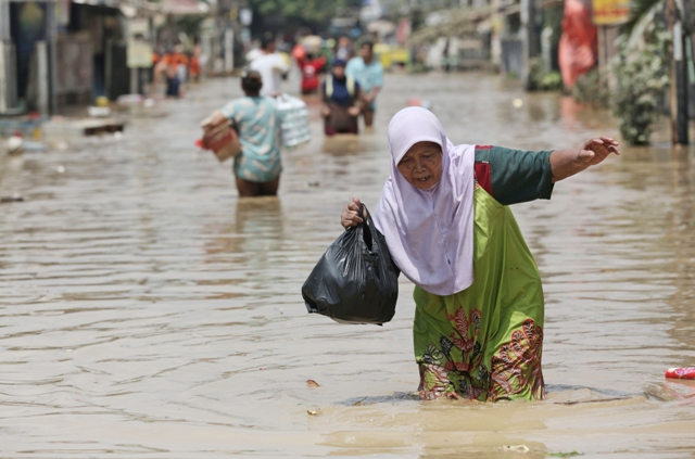 Indonézska žena sa brodí po zaplavenej ulici po prudkom lejaku v Bekasi na predmestí Jakarty