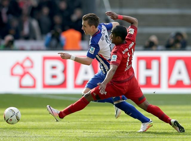 Futbalista Herthy Berlín Slovák Peter Pekarík (biely dres) a hráč Bayernu Mníchov Douglas Costa bojujú o loptu v zápase nemeckej Bundesligy Hertha Berlín - Bayern Mníchov