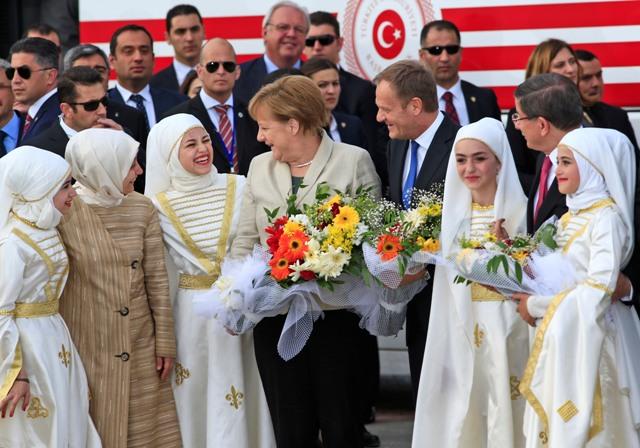 Nemecká kancelárka Angela Merkelová (uprostred), predseda Európskej rady Donald Tusk (štvrtý sprava) sa rozprávajú s mladými ženami počas návštevy utečeneckého tábora v meste Gaziantep na juhu Turecka, neďaleko sýrskych hraníc