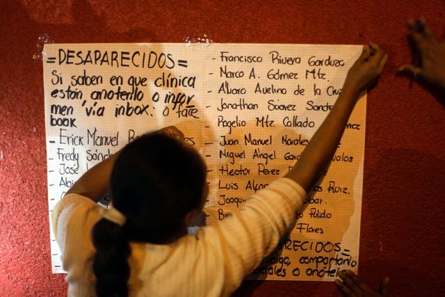Na snímka príbuzná  pripevňuje lepiacou páskou zoznam nezvestných pracovníkov na stenu miestnej nemocnice v meste Coatzacoalcos