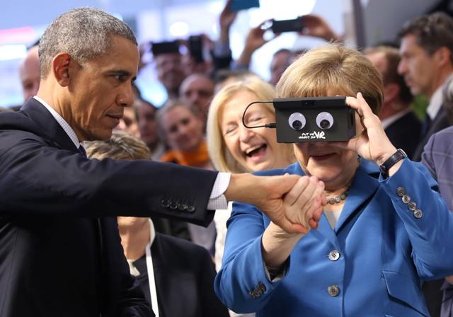 Americký prezident Barack Obama  drží za ruku nemeckú kancelárku angelu Merkelovú, ktorá testuje VR okuliare na Hannoverskom veľtrhu v Hannoveri