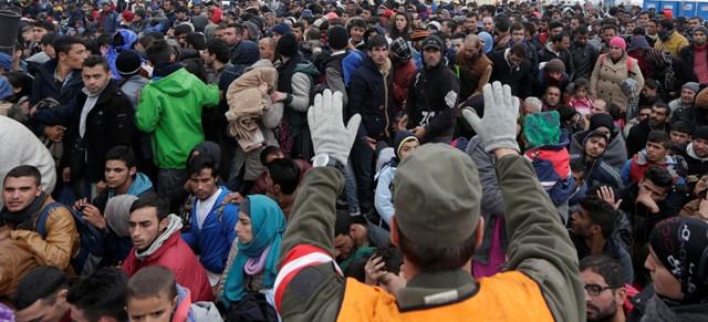 Snímka z 22. októbra 2015, kedy rakúsky vojak sa snaží udržať poriadok s migrantami na hranici so Slovinskom v rakúskom Spielfelde