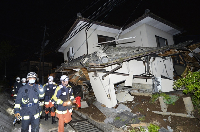 Na snímke hasiči a záchranári kontrolujú trosky zrúteného domu v meste Mašiki po zemetrasení na japonskom ostrove Kjúšu