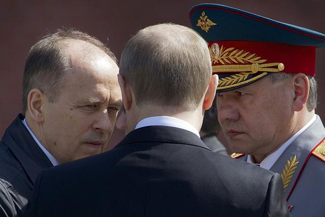 Ruský prezident Vladimir Putin (uprostred), šéf Federálnej bezpečnostnej služby Ruskej federácie (FSB) Alexander Bortnikov (vľavo) a šéf rezortu obrany Sergej Šojgu (vpravo)
