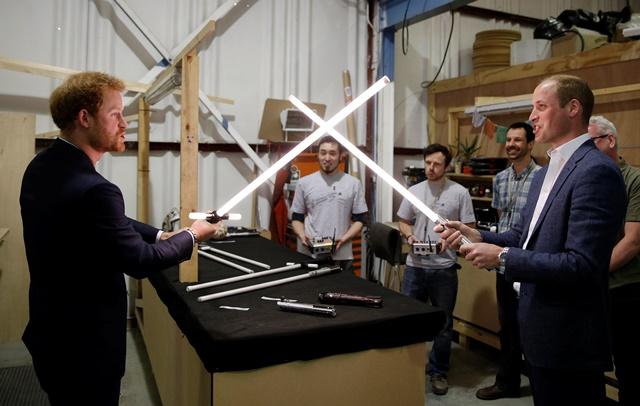 Na snímke britskí princovia Wiliam (vpravo) a Harry počas súboja s laserovými mečmi v rámci prehliadky filmových štúdií Pinewood neďaleko Londýna