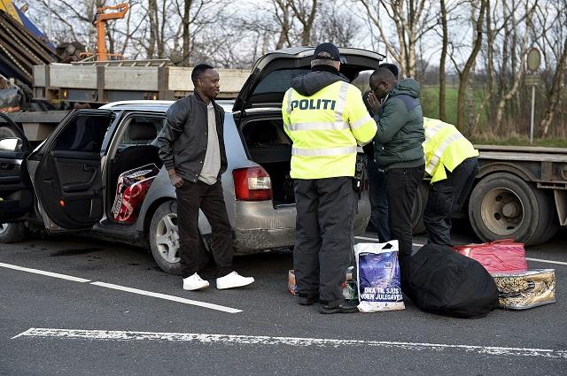 Dánski bezpečnostní pracovníci kontrolujú občianske preukazy pasažierov na cestnom hraničnom priechode na nemecko-dánskych hraniciach v Padborgu