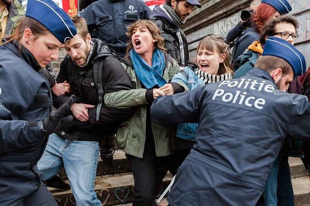Policajti zadržujú skupiny ľudí na námestí Place de la Bourse v centre Bruselu 2. apríla 2016.  Belgická polícia dnes na námestí Place de la Bourse v centre Bruselu zadržala najmenej dve desiatky ľudí, ktorí sa chceli zúčastniť na úradmi nepovolenej demonštrácii proti islamofóbii