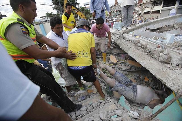 Na snímke dobrovoľníci vyťahujú zo sutín domu telo obete v prímorskom meste Pedernales v Ekvádore po silnom zemetrasení
