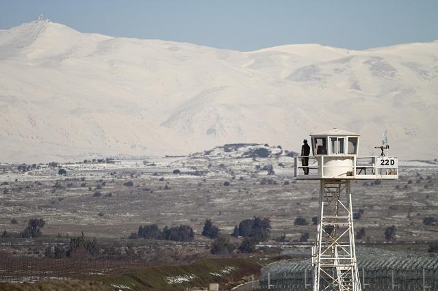 Na archívnej snímke vojenský príslušník OSN hliadkuje na stanovisku s výhľadom na  zasnežené Golanské Výšiny v blízkosti izraelsko-sýrskych hraníc