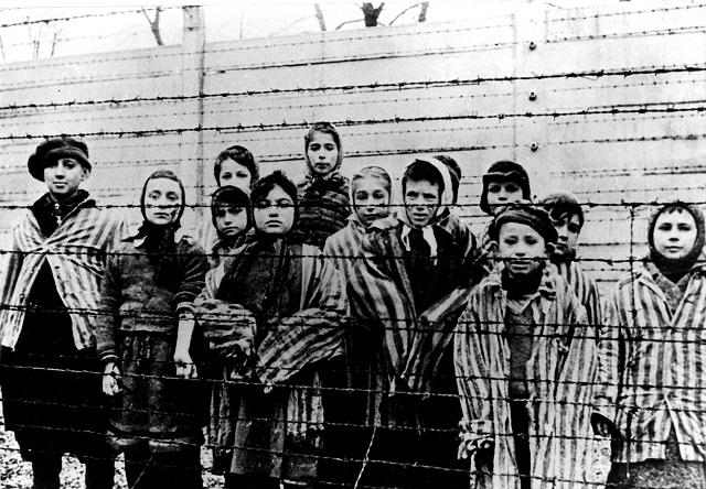Deti stoja za ostnatým drôtom v nacistickom koncentračnom  tábore v poľskom Osvienčime tesne po tom, ako tábor oslobodili sovietske jednotky