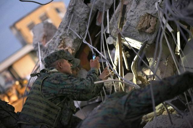 Vojak si svieti mobilom počas pátrania po preživších v troskách zrútenej budovy po silnom zemetrasení s magnitúdou 7,8 na ulici v Portovieju 18. apríla 2016