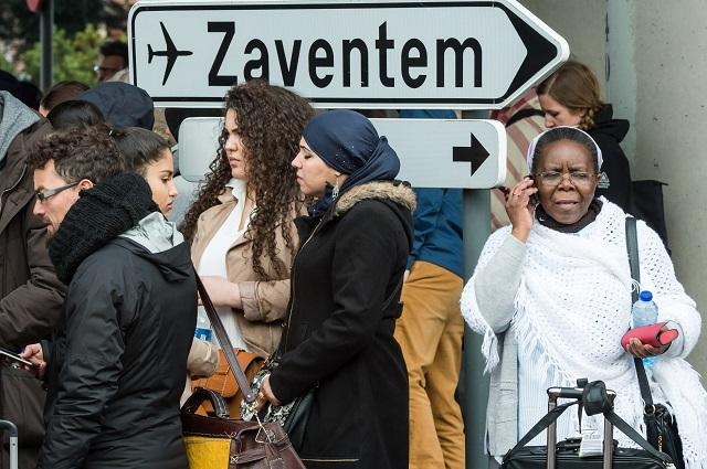 Na archívnej snímke ľudia stoja neďaleko letiska Zavantem po výbuchoch v Bruseli , ktoré sa odohrali 2. marca 2016