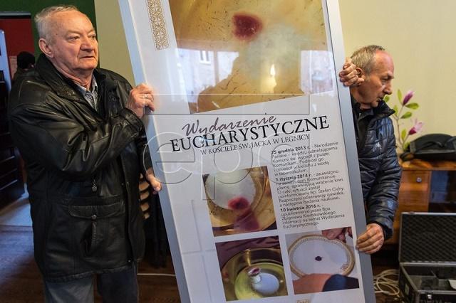 Na snímke veriaci počas tlačovej konferencie v kostole sv. Jaceka v Legnici 12. apríla 2016 nesú baner s informáciami o eucharistickom zázraku