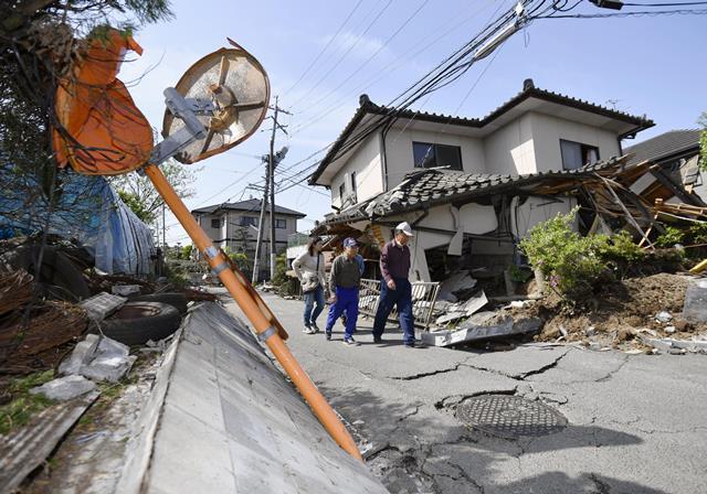 Na snímke obyvatelia kráčajú okolo zničeného domu po  zemetrasení s magnitúdou 6,5 na ulici v Mašiki na juhu Japonska