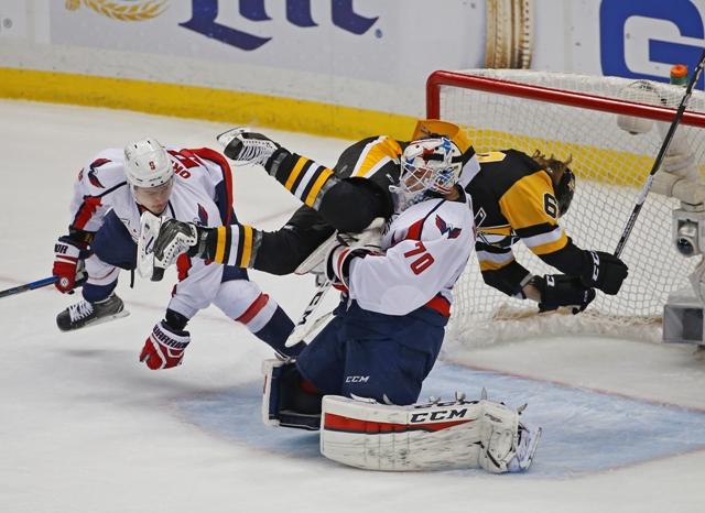Hráč Penguins Carl Hagelin naráža do brankára Capitals Bradena Holtbyho vo štvrtom zápase semifinále play off Východnej konferencie NHL Washington Capitals - Pittsburgh Penguins