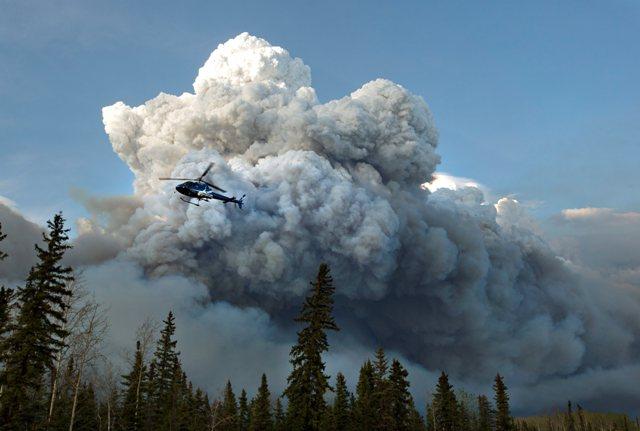 Hasičský vrtuľník letí pred obrovskými oblakmi dymu z lesných požiarov, ktoré si vynútili evakuáciu mesta Fort McMurray v kanadskej provincii Alberta