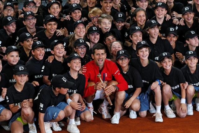 Srbský tenista Novak Djokovič (v červenom) pózuje s trofejou a zberačmi loptičiek po víťazstve vo finále mužskej dvojhry nad Britom Andym Murrayom na turnaji ATP Master 1000
