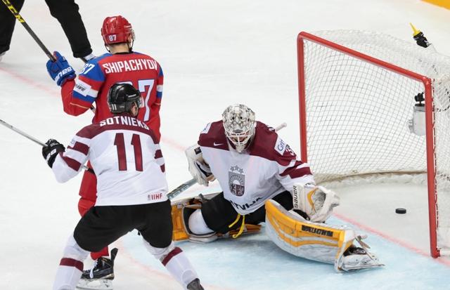 Na snímke vľavo hore ruský útočník Vadim Šipačov strieľa tretí gól Ruska, vpravo lotyšský brankár Elvis Merzlikins v zápase A-skupiny MS v hokeji Lotyšsko - Rusko v Moskve