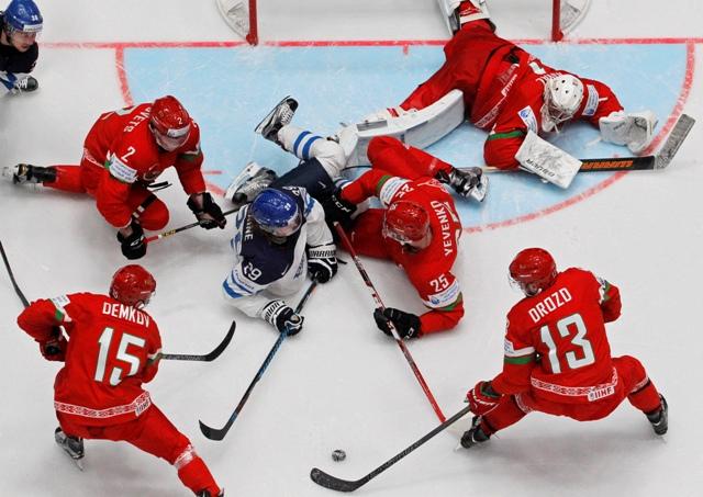 Fínsky hokejista Patrik Laine (uprostred vľavo) z Fínska bojuje o puk medzi hokejistami Bieloruska v zápase základnej B-skupiny  Fínsko - Bielorusko v Petrohrade