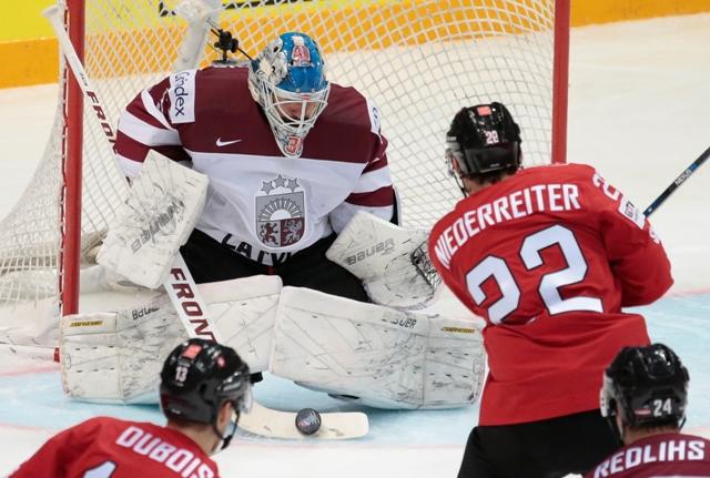 Na snímke vpravo hráč Švajčiarska Nino Niederreiter strieľa gól, vľavo lotyšský brankár Edgars Masalskis v zápase A-skupiny hokejových MS Švajčiarsko - Lotyšsko (5:4) v Moskve