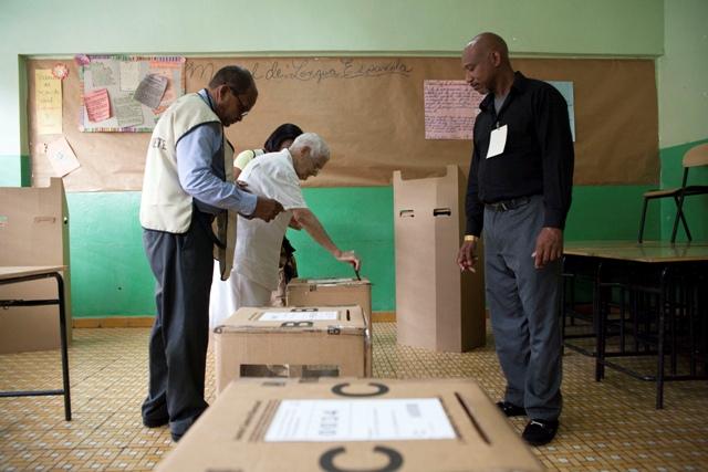 Na snímke volič vhadzuje hlasovací lístok do volebnej urny počas prezidentských a parlamentných volieb v Dominikánskej republike v Santo Domingu