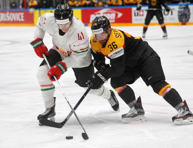 Maďarský hokejista Balázs Sebök (vľavo) a Nemec Yannic Seidenberg bojujú o puk v zápase základnej B-skupiny majstrovstiev sveta Nemecko - Maďarsko v Petrohrade