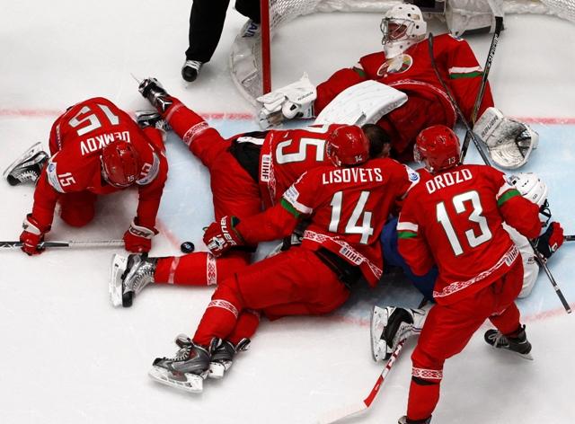 Bieloruskí hokejisti chránia svojho brankára v zápase základnej B-skupiny Bielorusko - Francúzsko v Petrohrade