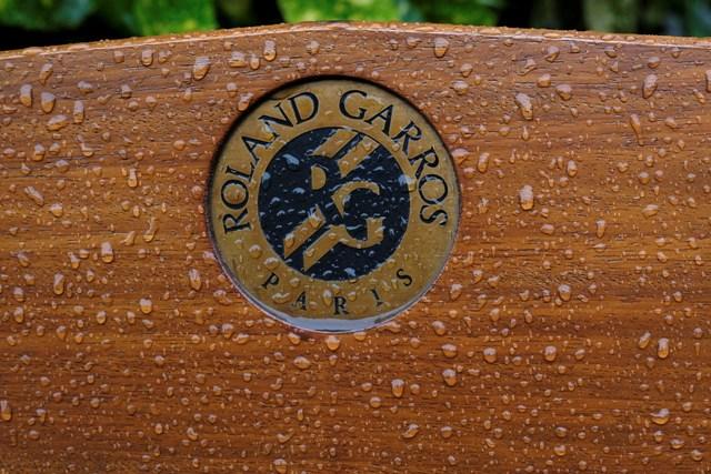 Dažďové kvapky sú na lavičke s logom Roland Garros na grandslamovom turnaji Roland Garros