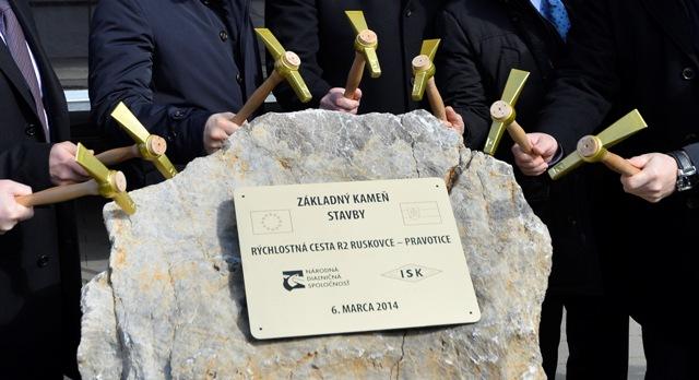 Snímka zo 6. marca 2014, kde hostia poklepávajú základný kameň počas slávnostného poklepania základného kameňa stavby Rýchlostná cesta R2 Ruskovce - Pravotice