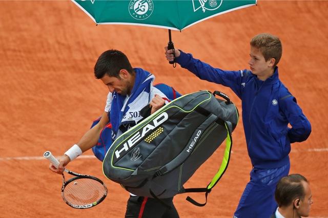 Svetová jednotka Srb Novak Djokovič odchádza z kurtu po prerušení zápasu proti Španielovi Robertovi Bautistovi Agutovi v osemfinále mužskej dvojhry na grandslamovom turnaji Roland Garros v Paríži