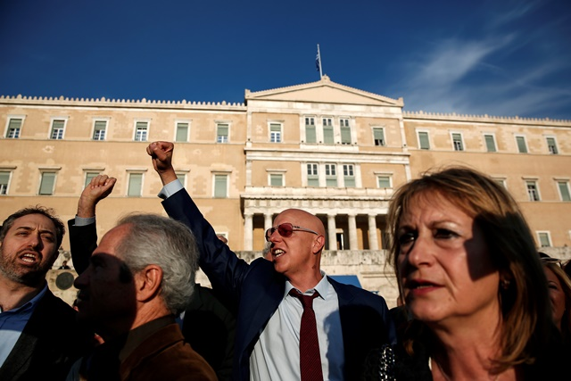 Na snímke protestujúci vykrikujú slogany pred budovou parlamentu v Aténach