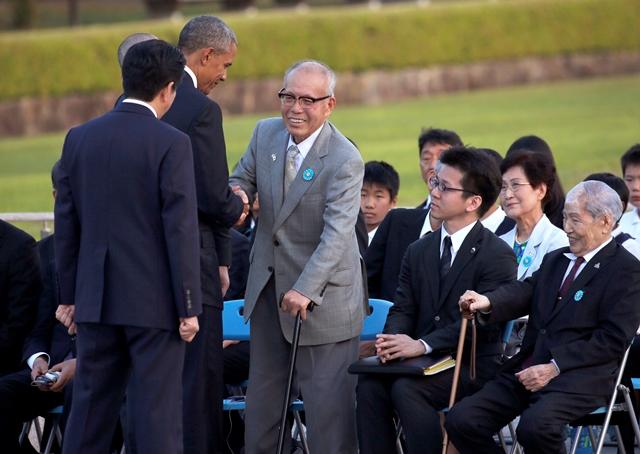 Na snímke prezident Obama podáva ruku historikovi Šigeakimu Morimu, vedľa neho sedí prekladateľ a vpravo Sunao Tsuboi