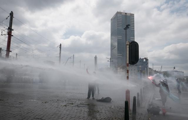 Na snímke policajti používajú vodné delo na protestujúcich počas protestu proti úsporným opatreniam stredopravej vlády v Bruseli