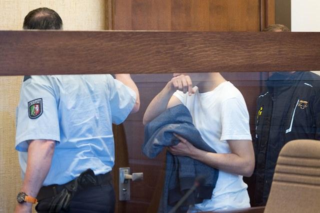 Na snímke nemeckí policajti vedú 26-ročného Alžírčana, ktorého meno nebolo zverejnené, do súdnej siene v Kolíne nad Rýnom