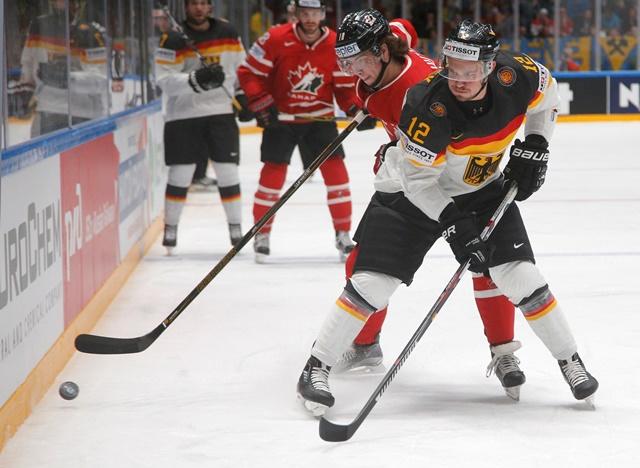 Na snímke hráč Kanady Ben Hutton (vľavo) a hráč Nemecka Patrick Hager (vpravo) v súboji o puk
