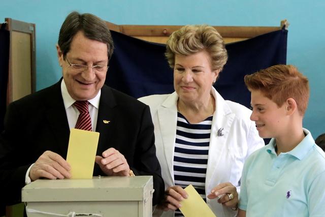 Na snímke cyperský prezident Nicos Anastasiades (vľavo) spoločne s manželkou Andri ( v strede) a vnukom Andim hádže volebné lístky do schránky vo volebnej miestosti v cyperskom Limassole