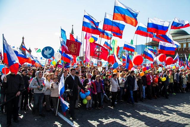 Na snímke Rusi mávajú zástavami a skandujú počas prvomájových osláv na Červenom námestí v Moskve