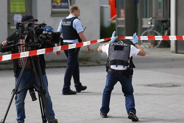 Kameraman filmuje  pred reštauráciou neďaleko železničnej stanice v Grafingu pri Mníchove 10. mája 2016, kde muž zaútočil na dvoch ľudí po útoku nožom v regionálnom vlaku