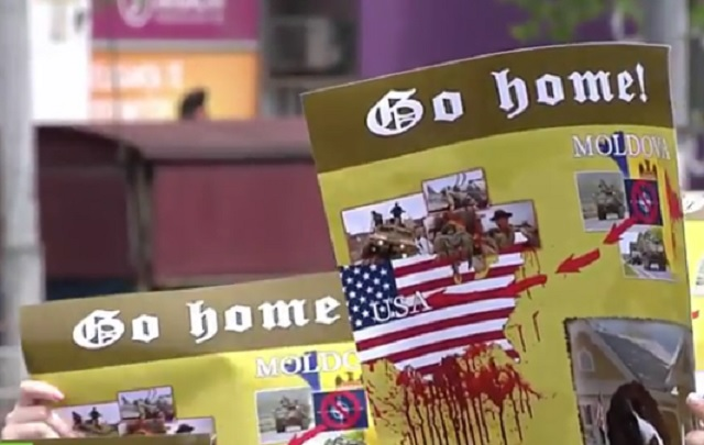 Transparent protestujúcich v Kišiňove proti vojskám NATO v Moldavsku