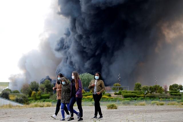 Na snímke ženy s ochrannými rúškami na tvári kráčajú po ulici neďaleko stúpajúceho čierneho dymu z horiacej skládky pneumatík